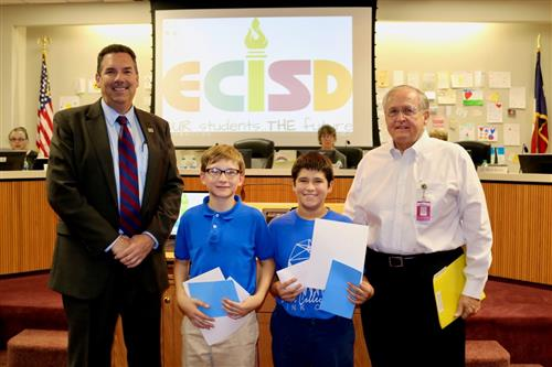 The two boys pose with the superintendent and a school board trustee after leading the pledges.