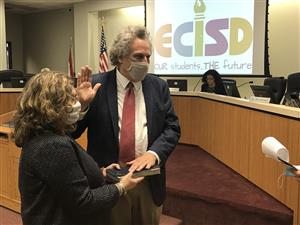 Chris Stanley, right hand raised and left hand on a Bible, takes the Oath of Office for ECISD.