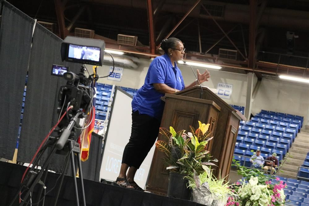 Loretta Walker standing at a podium, speaking during Convocation in August.