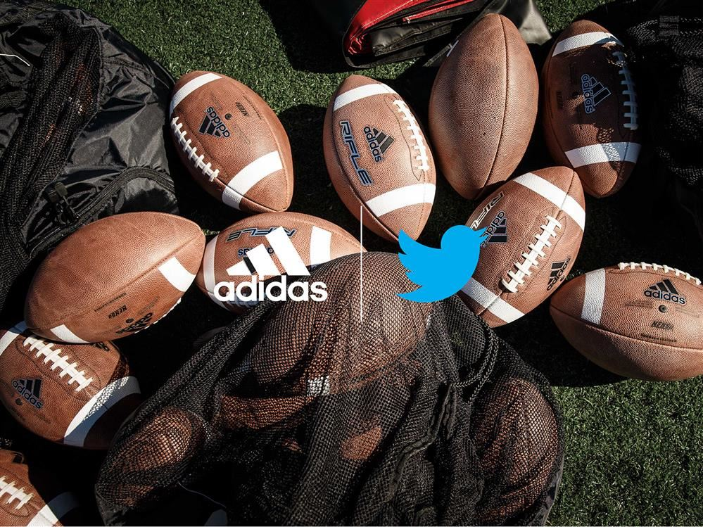 footballs laying on a turf field with the adidas and Twitter logos superimposed on them